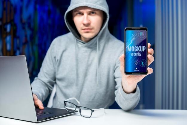 Mann an seinem schreibtisch mit dem digitalen sicherheitsmodell des mobiltelefons