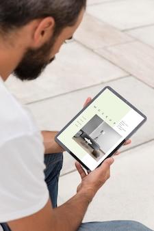Mann auf der straße mit tablette, die online liest