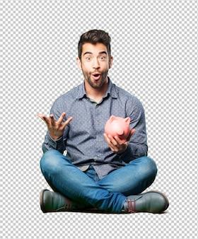 Mann, der auf dem fußboden mit einem sparschwein sitzt
