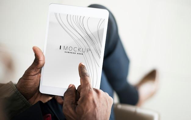 Mann, der auf einer tablette mit einem bildschirmmodell spielt