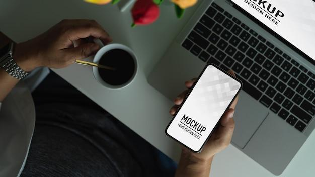 Mann, der das leere bildschirm-smartphone des modells hält, während kaffeetasse auf arbeitstisch hält