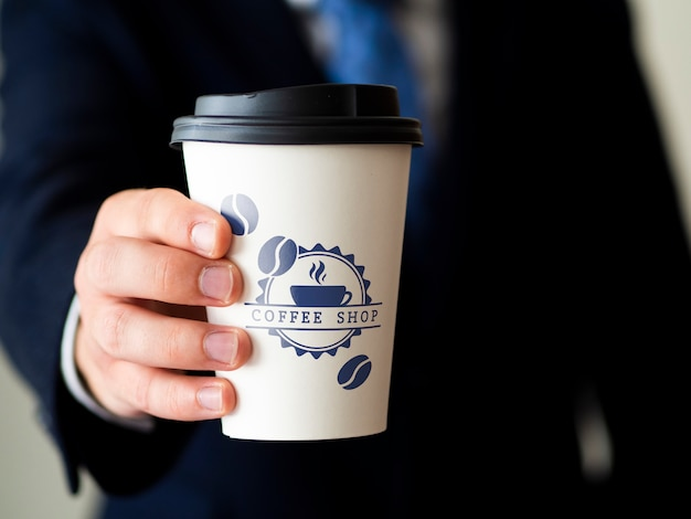 Mann, der ein kaffeetassenmodell hält