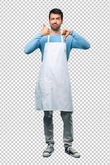 Mann, der ein schutzblech trägt, das gut-schlechtes zeichen macht. unentschlossene person zwischen ja oder nein