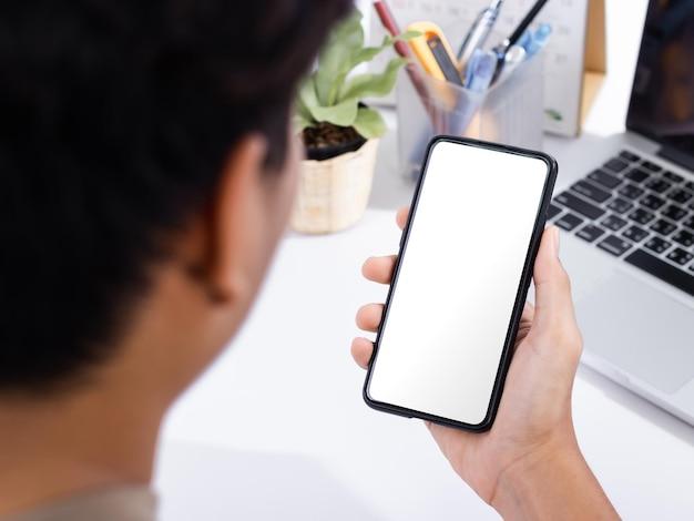 Mann, der ein smartphone-bildschirmmodell am weißen schreibtisch verwendet