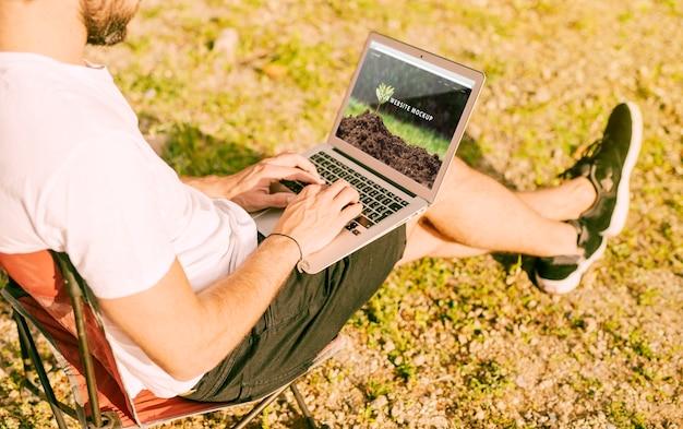 Mann, der laptopmodell in der natur verwendet