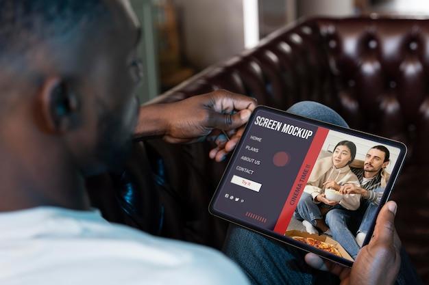 Mann, der netflix auf einem mock-up-bildschirm anschaut