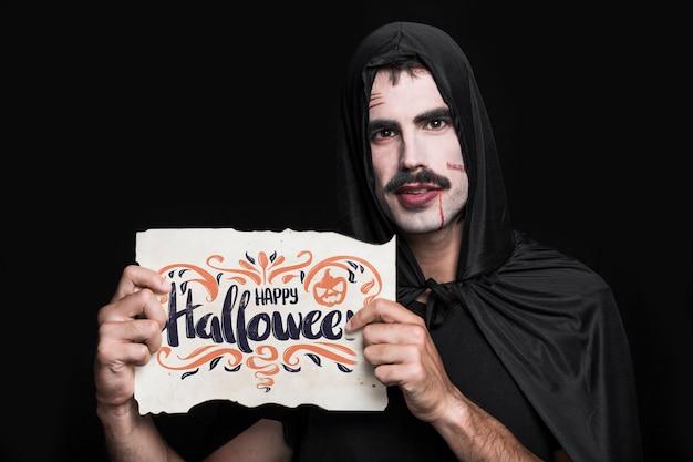 Mann, der papier mit halloween-beschriftung hält