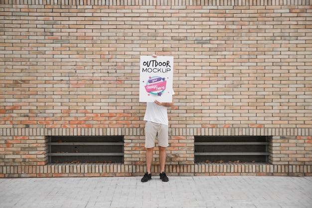 Mann, der plakatmodell vor backsteinmauer hält