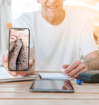 Mann, der smartphone-modell zeigt