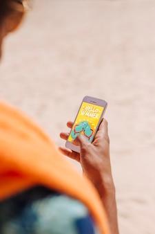 Mann, der smartphonemodell am strand verwendet