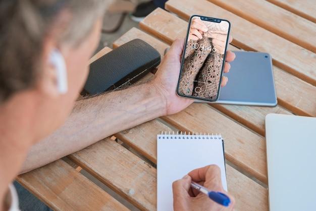Mann, der smartphonemodell betrachtet