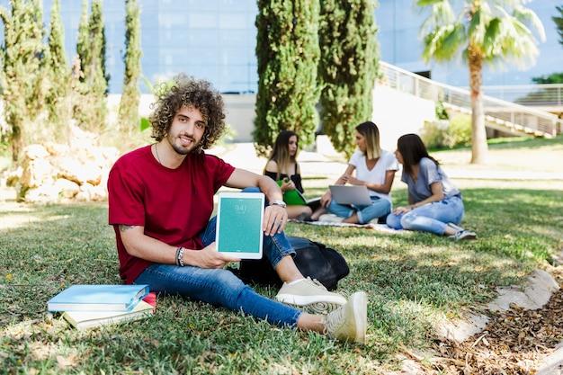 Mann, der tablettenmodell im park zeigt