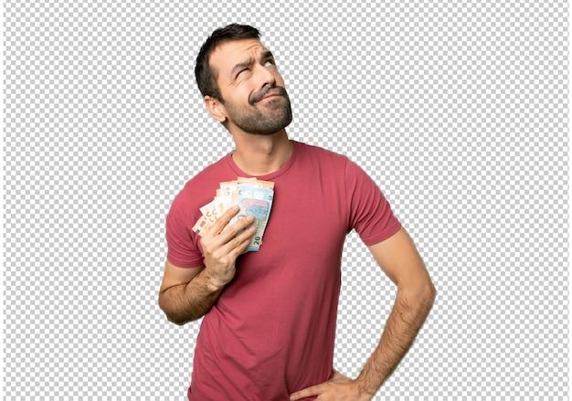 Mann, der viel geld mit ernstem gesicht oben schaut
