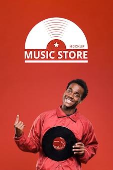 Mann hält vinylscheibe für musikgeschäft modell und zeigt nach oben