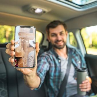 Mann im auto, das smartphonemodell zeigt