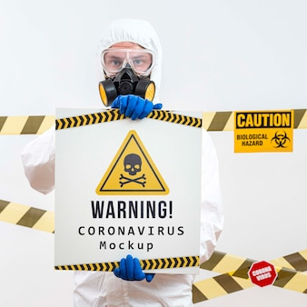 Mann im schutzanzug hält ein warnendes coronavirus-modell