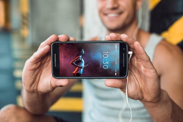 Mann in der turnhalle, die smartphonemodell hält