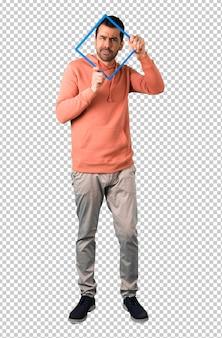 Mann in einem rosa sweatshirt, das durch leeren bilderrahmen vor dem gesicht und überrascht schaut