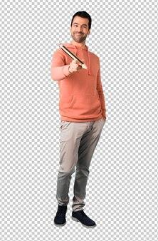 Mann in einem rosa sweatshirt, das einen großen bleistift hält