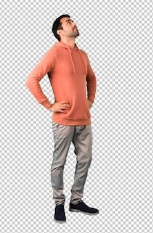 Mann in einem rosa sweatshirt, das zur seite steht und schaut