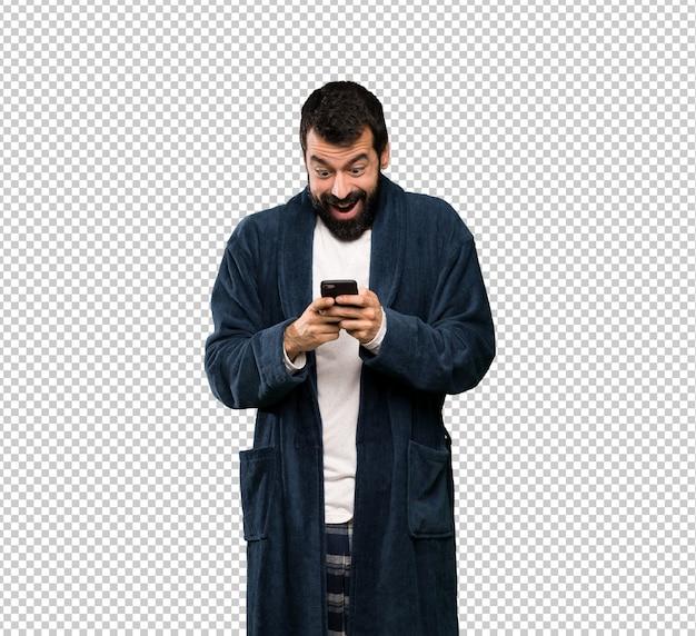 Mann mit bart im pyjama überrascht und eine nachricht senden