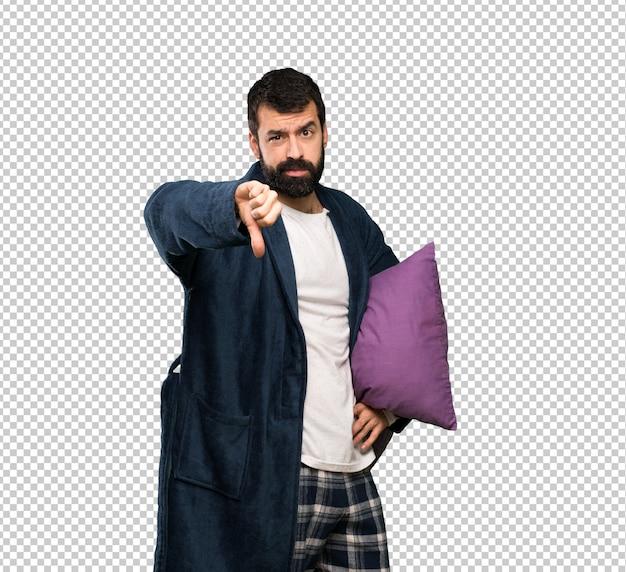 Mann mit bart in den pyjamas, die unten daumen mit negativem ausdruck zeigen