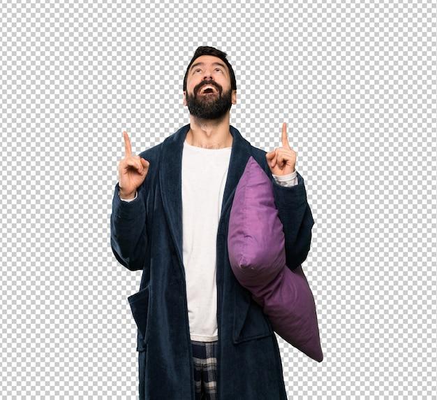Mann mit bart in den pyjamas überrascht und oben zeigend