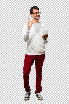 Mann mit brille und hörender musik, die ein okayzeichen mit den fingern beim blinzeln eines auges zeigt