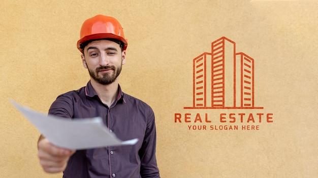 Mann mit dem schutzhelm, der ein unscharfes papier hält