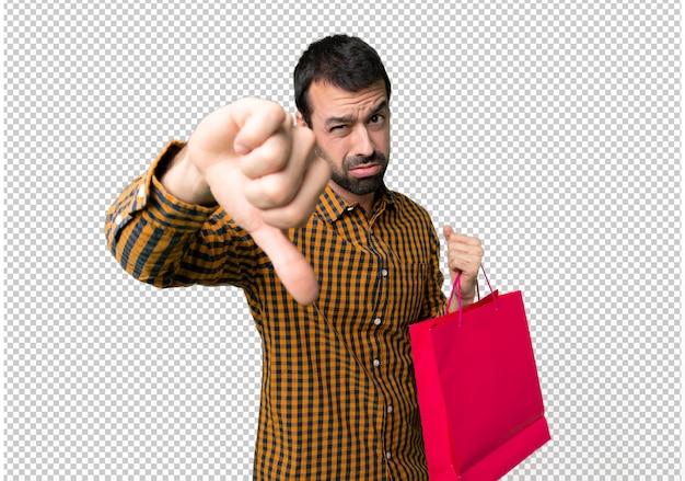 Mann mit den einkaufstaschen, die unten daumen mit negativem ausdruck unterzeichnen