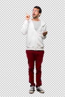 Mann mit den gläsern und hörender musik, die eine idee oben den finger zeigend steht und denkt