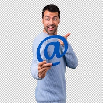 Mann mit der blauen strickjacke, die ikone von an punkt com hält