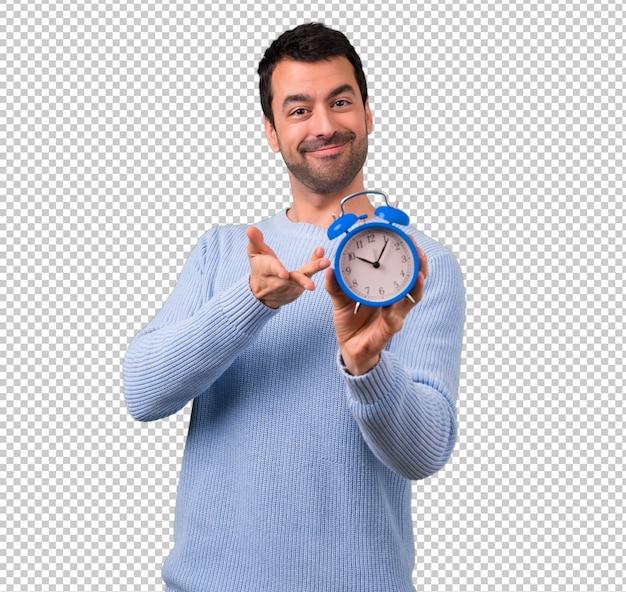 Mann mit der blauen strickjacke, die weinleserwecker hält