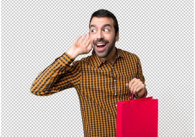 Mann mit einkaufstüten auf etwas zu hören, indem sie hand auf das ohr setzen