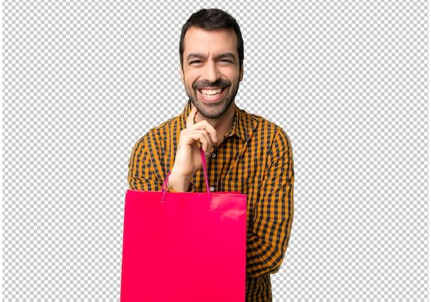 Mann mit einkaufstüten lächelnd mit einem süßen ausdruck