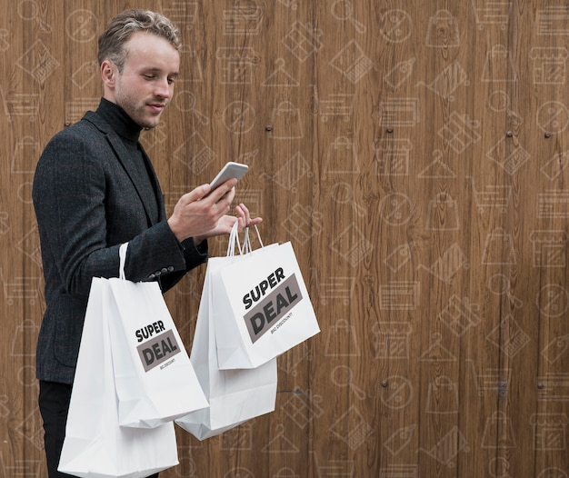 Mann mit einkaufstüten telefon überprüfend