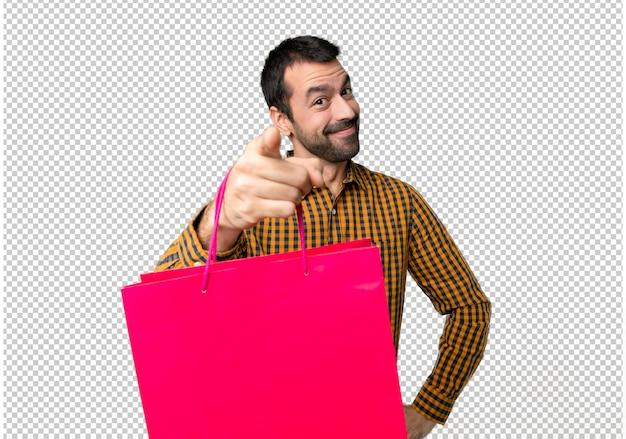 Mann mit einkaufstüten zeigt finger auf sie mit einem überzeugten ausdruck