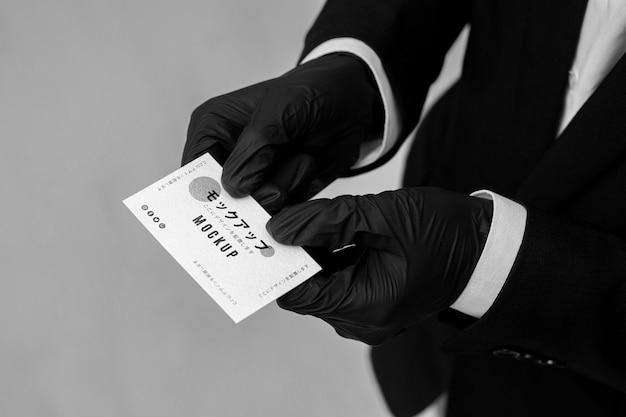 Mann mit handschuhen, die ein visitenkartenmodell halten