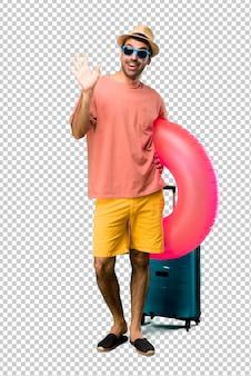 Mann mit hut und sonnenbrille auf seinen sommerferien begrüßend mit der hand mit glücklichem ausdruck