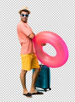 Mann mit hut und sonnenbrille auf seinen sommerferien die arme halten gekreuzt in seitlicher position beim lächeln. zuversichtlicher ausdruck