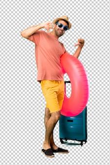 Mann mit hut und sonnenbrille auf seinen sommerferien, die daumen zeigen, unterzeichnen unten mit negativem ausdruck. trauriger ausdruck