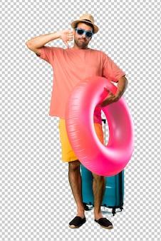 Mann mit hut und sonnenbrille auf seinen sommerferien, die unten daumen mit beiden händen zeigen. negativer ausdruck