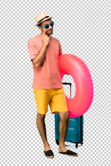 Mann mit hut und sonnenbrille auf seinen sommerferien, die zur front stehen und schauen, die das auge mit dem finger öffnet