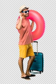 Mann mit hut und sonnenbrille auf seinen sommerferien etwas hörend, indem sie hand auf das ohr setzen