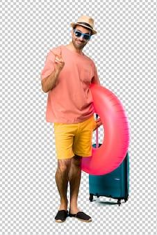 Mann mit hut und sonnenbrille auf seinen sommerferien glücklich und zwei mit den fingern zählend
