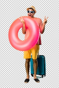 Mann mit hut und sonnenbrille auf seinen sommerferien lächelnd und siegeszeichen mit beiden händen und mit einem freundlichen gesicht zeigend