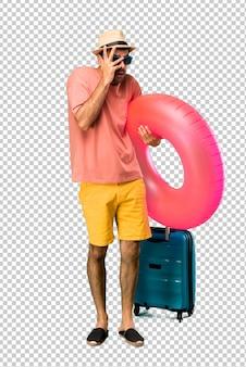 Mann mit hut und sonnenbrille auf seinen sommerferien überrascht und bedeckung mit den händen beim schauen durch die finger