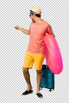 Mann mit hut und sonnenbrille auf seinen sommerferien zurück zeigend mit dem zeigefinger, der ein produkt darstellt