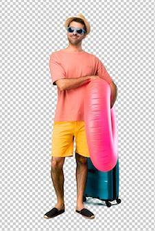 Mann mit hut und sonnenbrille in seinen sommerferien die arme in frontaler position gekreuzt halten. zuversichtlicher ausdruck