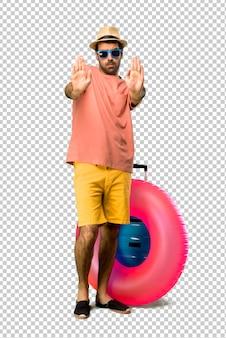 Mann mit hut und sonnenbrille in seinen sommerferien machend, stoppen sie geste mit ihrer hand für enttäuscht mit einer meinung